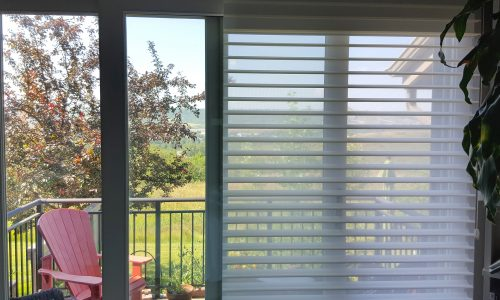 Bedroom deck with sheer horizontal blinds. One side up. One side down.