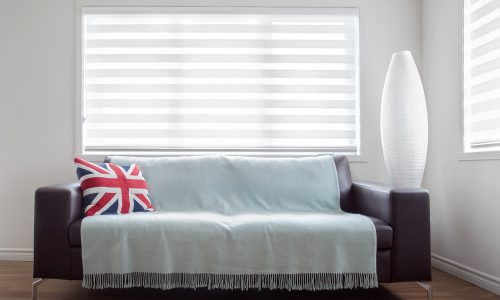 Horizontal image of  a modern leather sofa with throw and a Union Jack pillow, in bright living room. Space for copy.